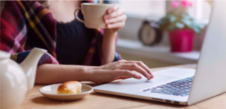A young woman uses her laptop at home while she enjoys a coffee and a croissant.
