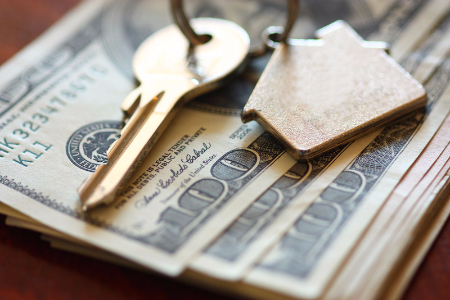 Keys for a home laying over money.