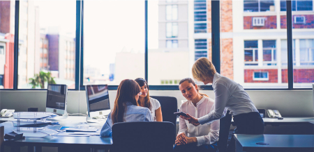 A group of business women conversing in a formal office setting.